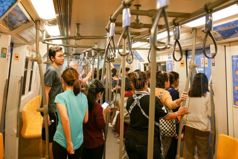БАНГКОК, ТАИЛАНД - 29-ОЕ ДЕКАБРЯ 2017: Много людей сидят в поезде для ожидания следующей станции стоковое изображение rf