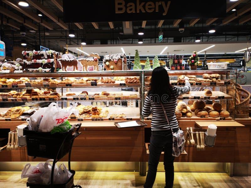 БАНГКОК, ТАИЛАНД - 31-ОЕ ДЕКАБРЯ: Хлеб неопознанной женщины покупая в магазине пекарни 31-ого декабря 2018 в Бангкоке, Таиланде стоковые изображения