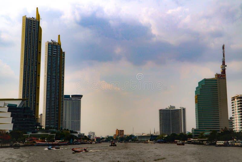 Бангкок, Таиланд - 18-ое мая 2019: Горизонт ландшафта на реке Chao Pra Ya со шлюпкой, пристанью, башней и небоскребами Бангкоком  стоковое изображение rf