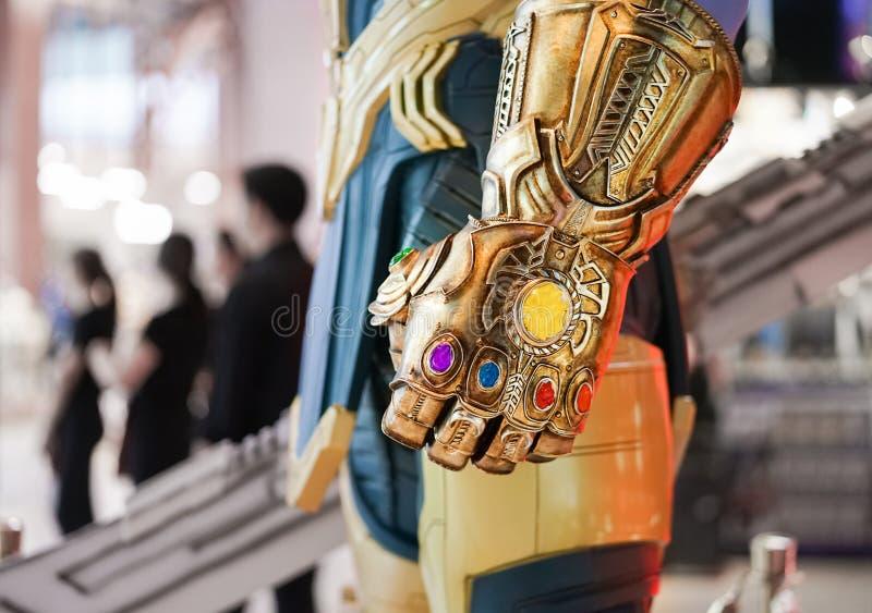 Бангкок, Таиланд - 4-ое мая 2019: Закрытое поднимающее вверх фото камней перчатки шпицрутена золота Thanos светящих Thanos супер  стоковые изображения rf