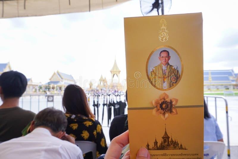 Бангкок, Таиланд - 10-ое ноября 2017: Посетитель держа брошюру в шатре ждать для того чтобы войти королевский крематорий для коро стоковое изображение rf