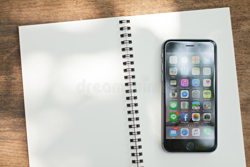 БАНГКОК, ТАИЛАНД - 22-ОЕ ФЕВРАЛЯ 2016: Новые appication iPhone 6 показывая положило дальше блокнот iPhone самый популярный smartp стоковое фото rf