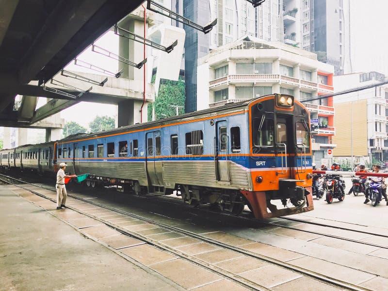 Бангкок, Таиланд - 6-ое января 2018: Флаги поезда стоят штатом, который развевая пока поезд бежал через дорогу Много автомобилей  стоковое фото rf