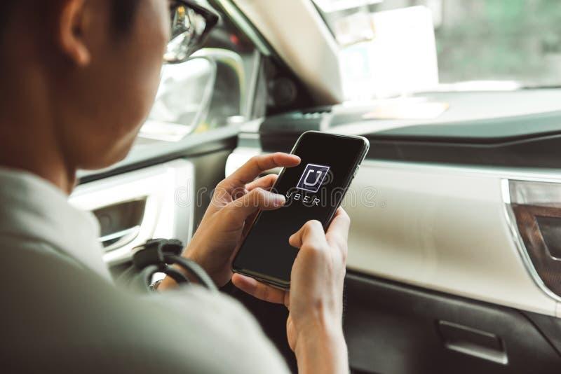 БАНГКОК, ТАИЛАНД - 22-ОЕ ЯНВАРЯ: Человек используя Uber app на smartpho стоковое изображение rf