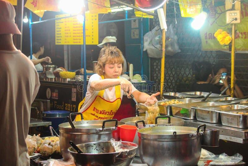 БАНГКОК, ТАИЛАНД - октябрь 2017: Довольно тайская женщина варя еду в стойле улицы дороги Yaowarat, Чайна-тауна стоковое изображение