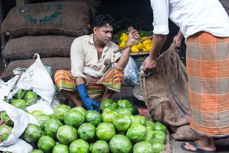 Бангладешский человек продавая папапайю на рынке, dhaka, karwanbazar, стоковые фото