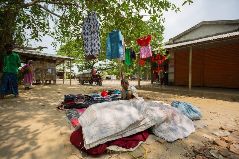Бангладеш - 19 мая 2019 года: Сельский бизнесмен продает одежду и продукты, чтобы повесить их на ствол дерева, Мехерпур, стоковое изображение