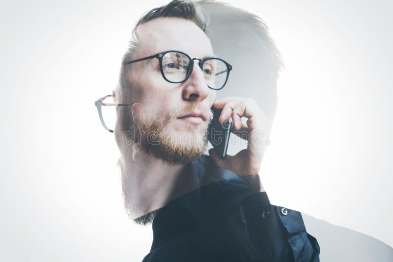 Банкир двойной экспозиции бородатый нося черную рубашку и стекла, держа современную руку smartphone Изолированная белизна, челове стоковые фото