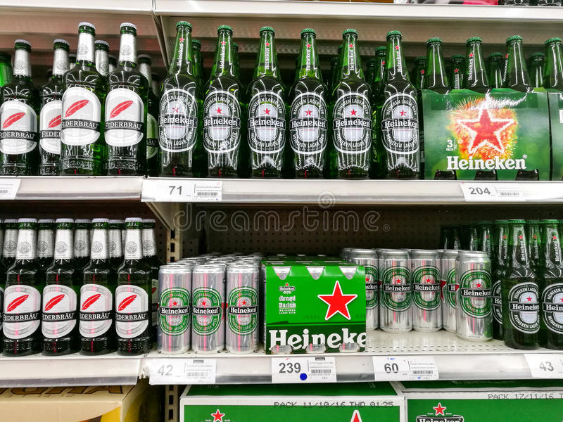 Банки пива и бутылки Heineken стоковое фото