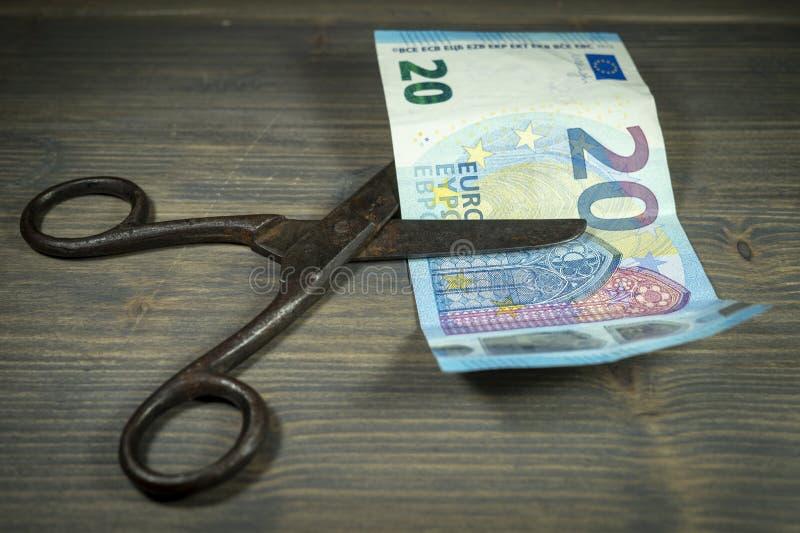 Банкнота евро отрезка ножниц над зеленой предпосылкой стоковое изображение