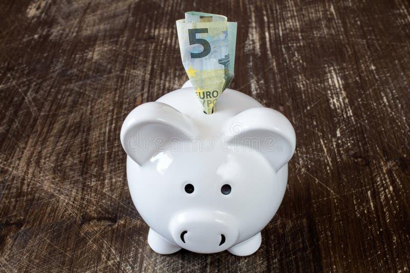 Банкнота копилки и евро 5 стоковая фотография