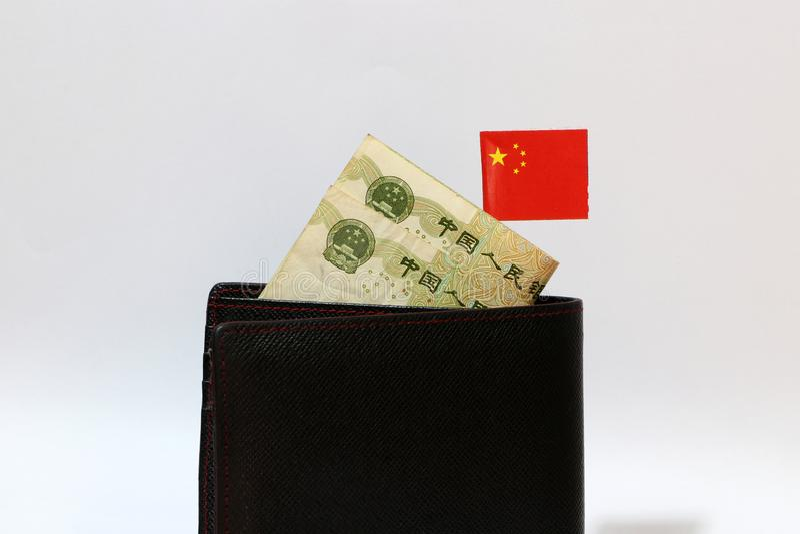 Банкнота юаней Китая и мини ручки флага китайской нации на черном бумажнике с белой предпосылкой стоковые изображения rf