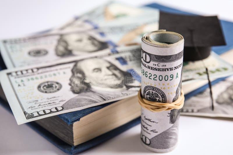 Банкноты доллара, мини-дипломная шляпа и книга о белом Концепция платы за обучение стоковая фотография rf