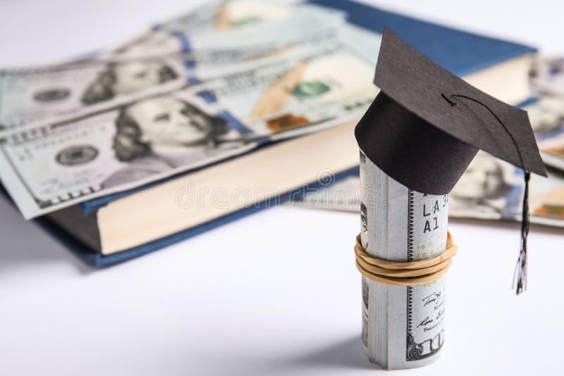 Банкноты доллара с мини-шляпой для выпускного и книжкой на заднем плане Концепция платы за обучение стоковое фото rf