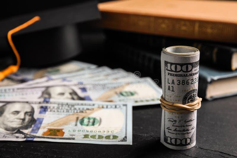 Банкноты доллара, шляпа для выпускного и книги на столе Концепция платы за обучение стоковые изображения