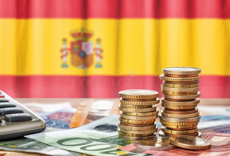 Банкноты евро и монетки перед национальным флагом Испании стоковые фото