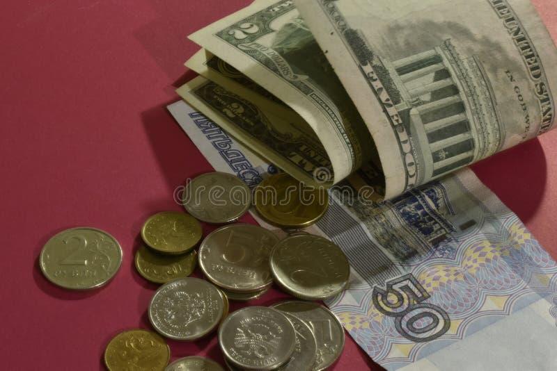Банкноты и монетки на красной предпосылке стоковое изображение rf