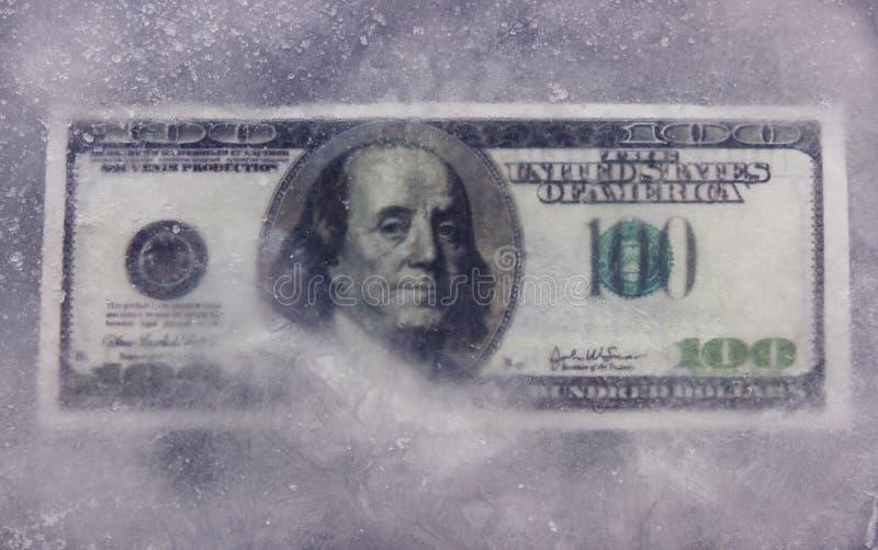 100 банкнот доллара, который замерли в льде стоковое изображение
