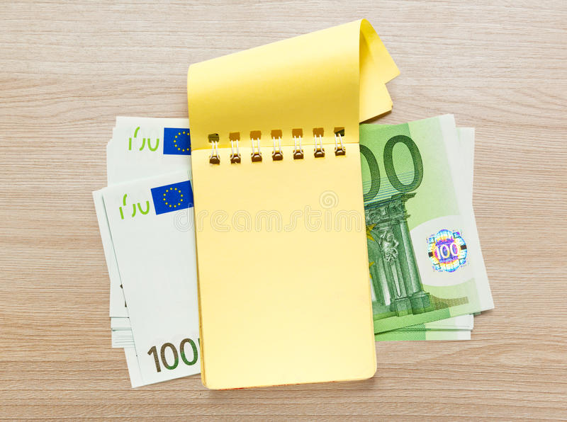 100 банкнот евро и желтого блокнот стоковая фотография