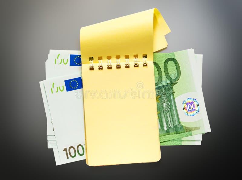 100 банкнот евро и желтого блокнот стоковые фото