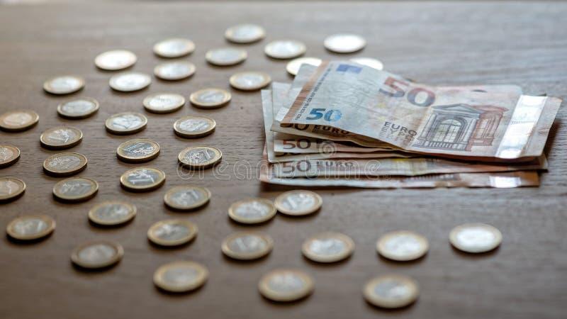 50 банкнот евро и монетки 1 евро на светлой деревянной предпосылке стоковая фотография