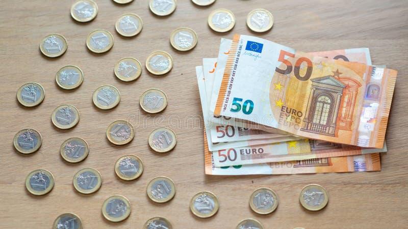 50 банкнот евро и монетки 1 евро на светлой деревянной предпосылке стоковое фото rf