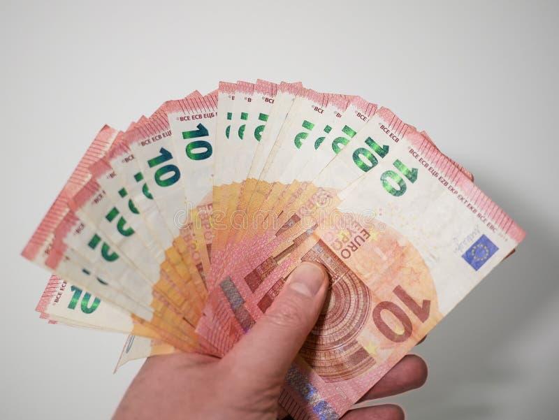 10 банкнот евро, который дуют вне в руке кавказского мужчины стоковое фото rf