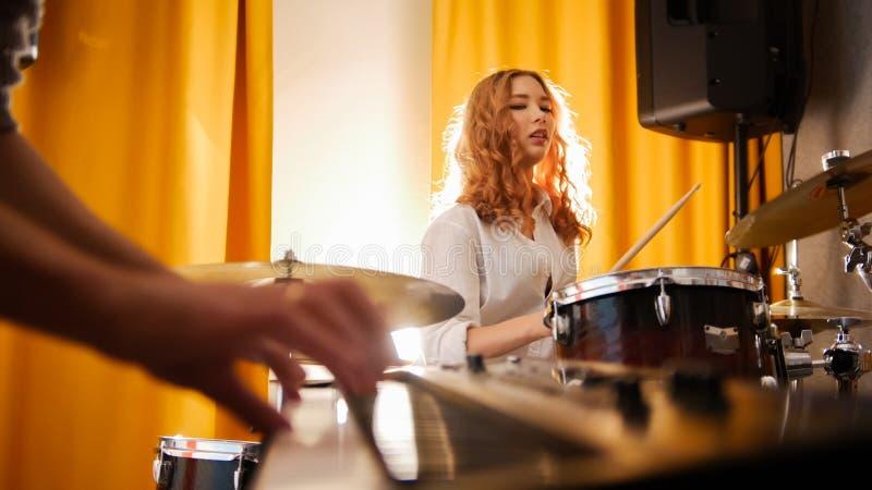 Барабанщик девушки и парень на клавиатурах Фокус от рук к барабанчикам Backlight стоковые фото