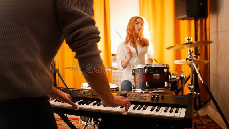 Барабанщик девушки и парень на клавиатурах Фокус от рук к барабанчикам стоковое фото