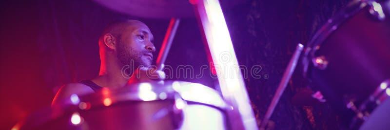 Барабанщик играя барабанчик в клубе стоковая фотография