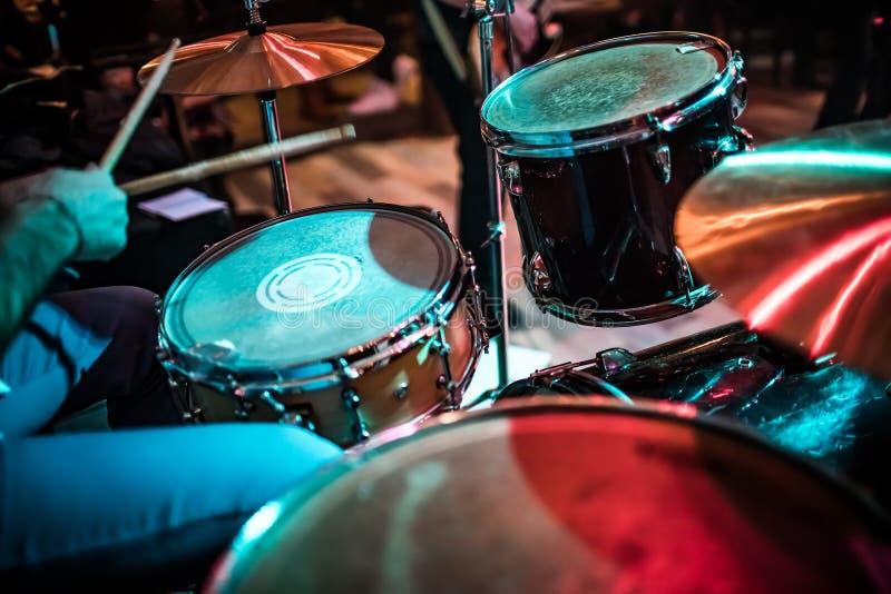 Барабанщик играя на барабанчике установленном на этап стоковое фото