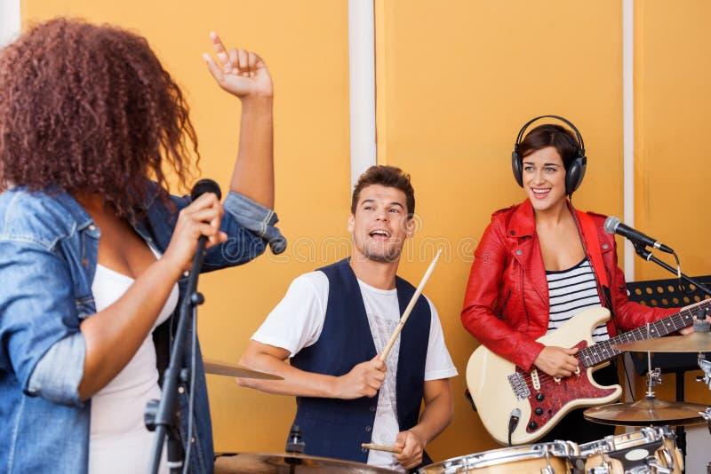 Барабанщик и гитарист смотря женщину поя внутри стоковые фото