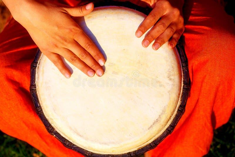 Барабанщик молодой дамы с ее барабанчиком djembe стоковая фотография