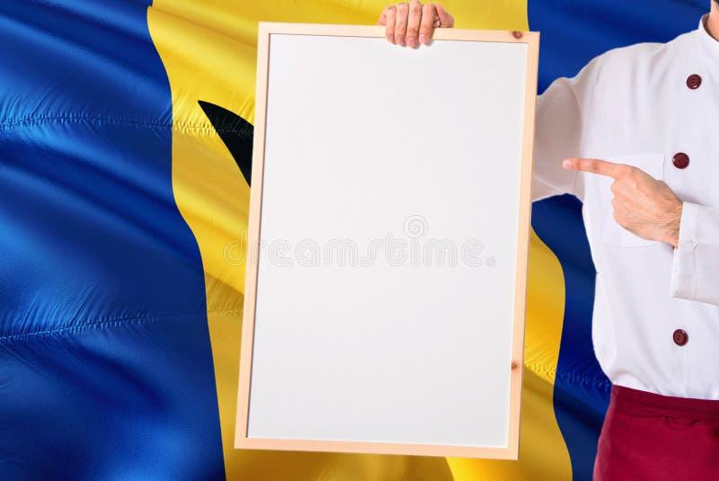 Барбадосский шеф-повар держа пустое меню whiteboard на предпосылке флага Барбадос Сварите нося форму указывая космос для текста стоковые изображения