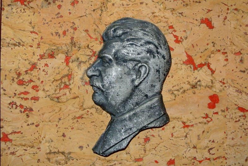 Барельеф Сталина на красной предпосылке Иосиф Сталин - русский революционер, советская политическая, положение, войска и партийны стоковая фотография rf