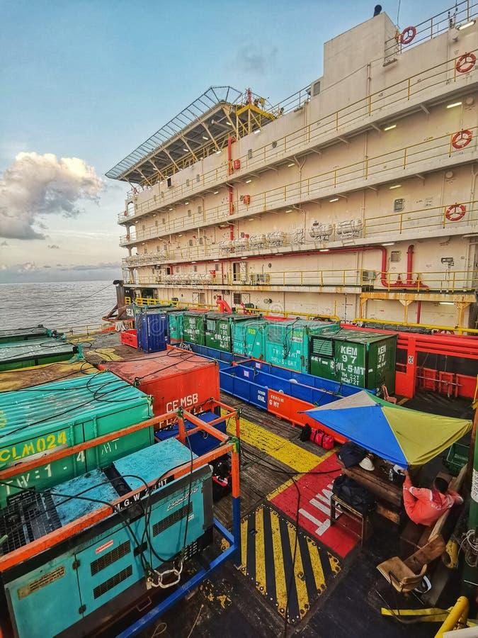 Баржа работы размещещния связанная к нефтяной платформе во время красивого захода солнца стоковое фото