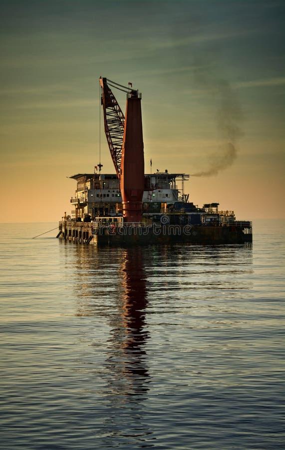 Баржа размещещния во время захода солнца на море стоковые фотографии rf