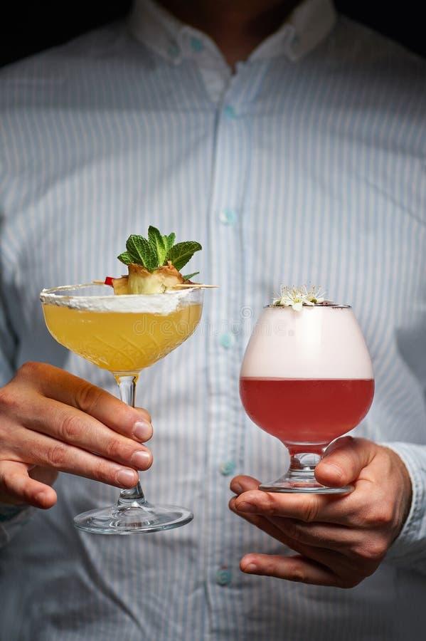 Бармен держит 2 различных коктейля лета в руках красные и желтые напитки в руках бармена стоковые фотографии rf
