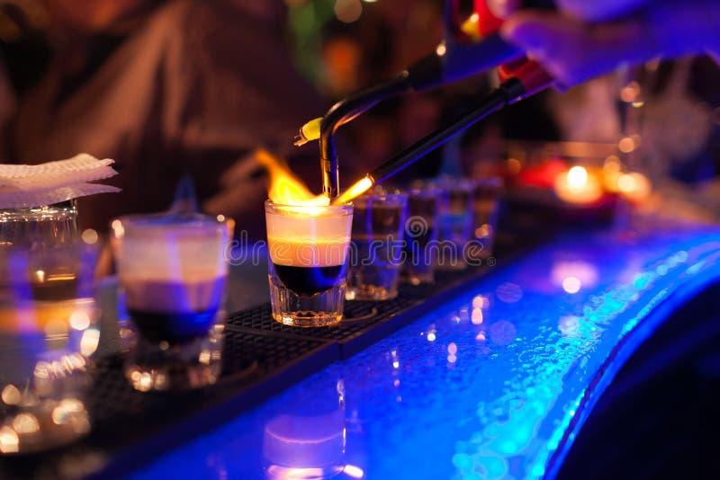 Бармен делает горячий спиртной коктеиль и воспламеняет бар ночной клуб элиты во время партии подготавливает пламенистый коктеиль стоковые фотографии rf