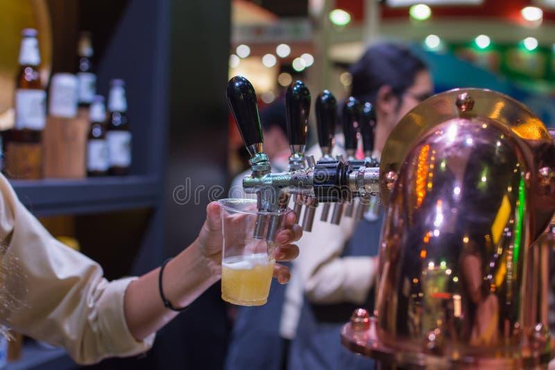 Бармен или бармен лить пиво лагера проекта от крана пива стоковая фотография rf
