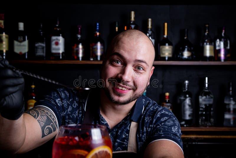 Бармен кладя к стеклу свежего и вкусного мира коктейля шприца Aperol льда стоковая фотография rf