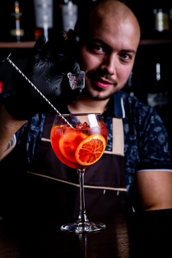 Бармен кладя к стеклу свежего и вкусного мира коктейля шприца Aperol льда стоковые изображения