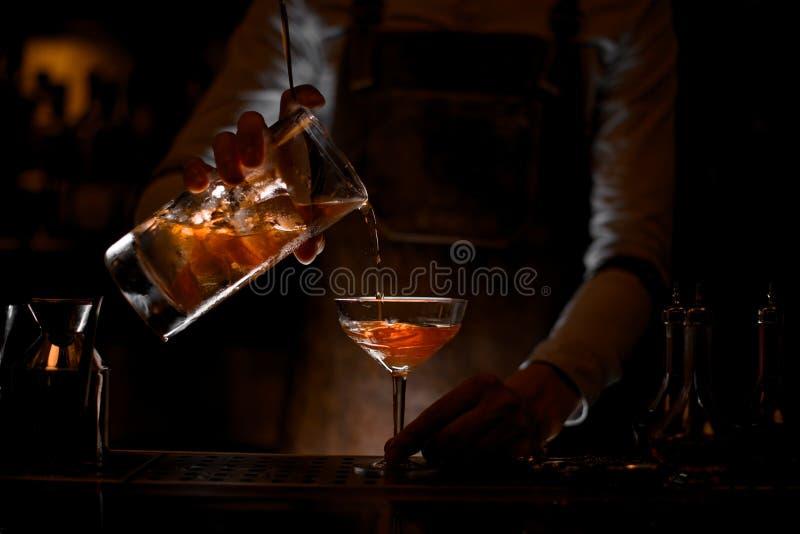 Бармен лить коктейль алкоголя со стрейнером стоковые фото