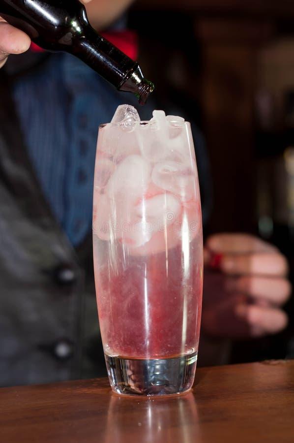Бармен лить красный сироп от бутылки в стекло с напитком и льдом алког стоковое изображение