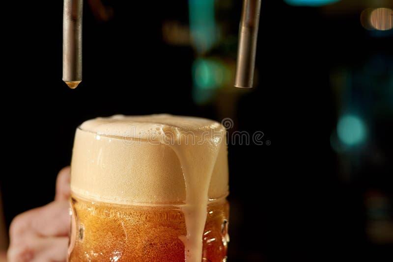Бармен лить свежее пиво в ночном клубе стоковые изображения rf