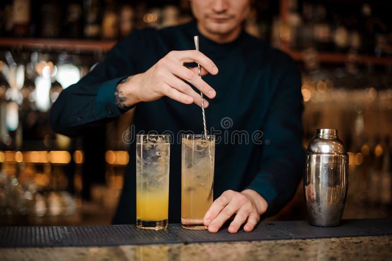 Бармен подготавливает 2 спиртных коктеиля, шевеля ингридиенты стоковые изображения