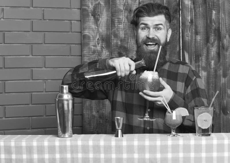 Бармен с бородой и счастливой стороной делает коктеиль, стоковая фотография rf