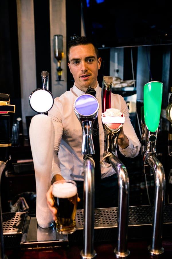 Бармен служа пинта пива стоковая фотография