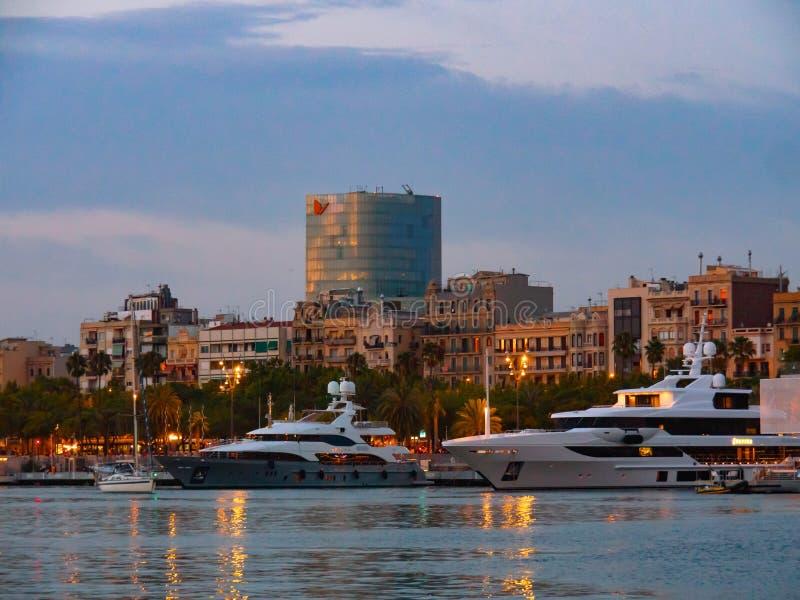 Барселона, Испания - август 2019 года: несколько белых лодок, пришвартованных к пристани, вид на море Дома и современное здание н стоковое изображение