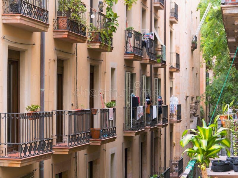 Барселона, Испания - август 2019 года: пейдж-здания с балконами, с видом на середину полотенца и зеленые растения на балконах с стоковое изображение